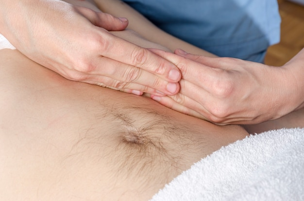 Fysiotherapeut doet een activering van het diafragma. massage voor een man-patiënt.