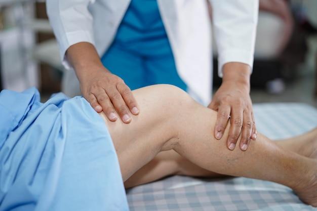 Fysiotherapeut doet fysiotherapie in revalidatie met patiënt in het ziekenhuis.