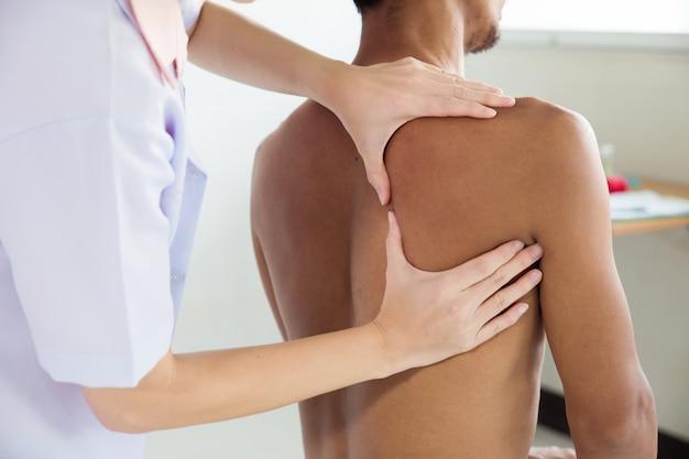 Fysiotherapeut doet genezende behandeling op de rug van de mens.