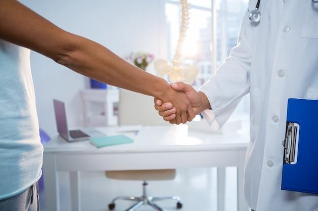Fysiotherapeut handen schudden met vrouwelijke patiënt