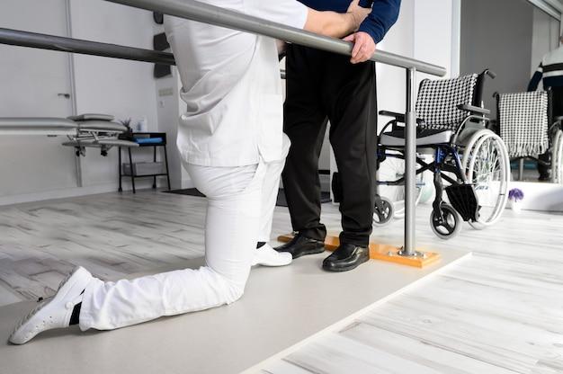 Fysiotherapeut helpt gehandicapte blanke senior man te lopen met parallelle staven in revalidatiecentrum.