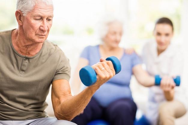 Fysiotherapeut helpt patiënten met oefeningen thuis