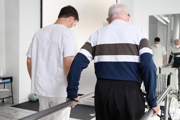 Fysiotherapeut helpt senior patiënt lopen tussen parallelle staven.
