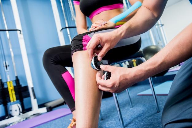 Fysiotherapeut installeert elektrostimulator op de spieren van de benen.