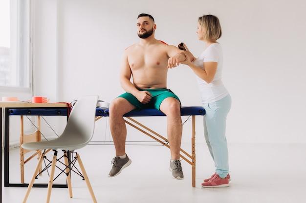 Fysiotherapeut kinesio tape toepassen op patiënten gewonde schouder