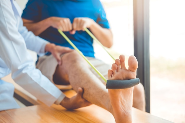 Fysiotherapeut man die weerstand band oefening geeft behandeling over knie van atleet