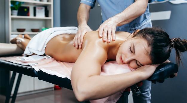 Fysiotherapeut massage geven aan een vrouw in de kliniek