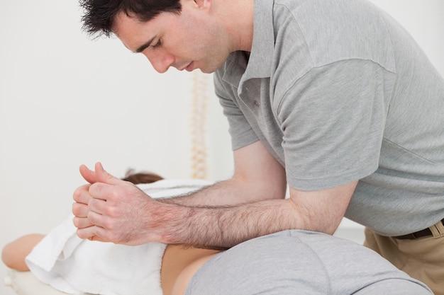 Fysiotherapeut masseert de rug van een patiënt met zijn onderarmen