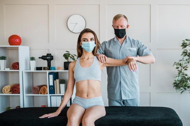 Fysiotherapeut medische masker dragen tijdens een therapiesessie met vrouw