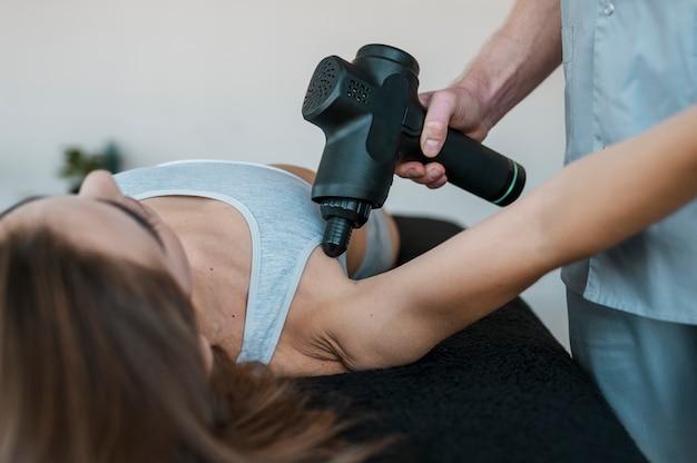 Fysiotherapeut met vrouwelijke patiënt en apparatuur tijdens een fysiotherapiesessie