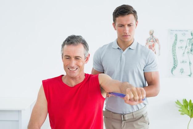 Fysiotherapeut onderzoekt een glimlachende volwassen mans arm