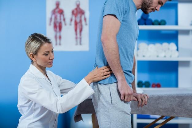 Fysiotherapeut onderzoekt mans terug