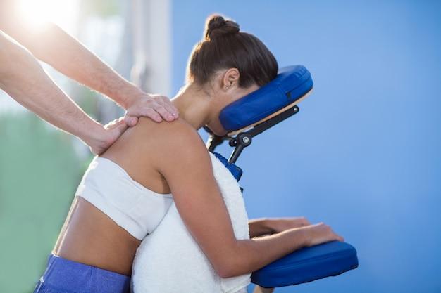 Fysiotherapeut schoudermassage geven aan een vrouwelijke patiënt