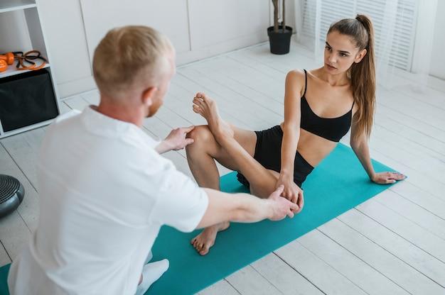 Fysiotherapeut tijdens behandelsessie met vrouwelijke patiënt