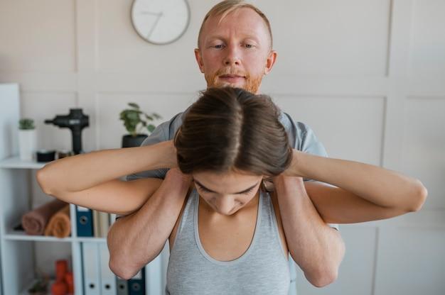 Fysiotherapeut tijdens een therapiesessie met vrouwelijke patiënt