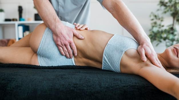 Fysiotherapeut uitvoeren van oefeningen op vrouwelijke patiënt
