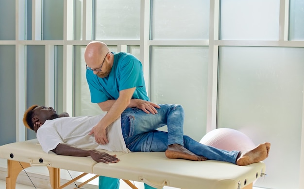 Fysiotherapeut voert een therapiesessie uit met een oudere man in een revalidatiecentrum sportfysio...