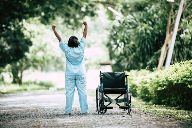 Fysiotherapie hogere vrouw met rolstoel in het park