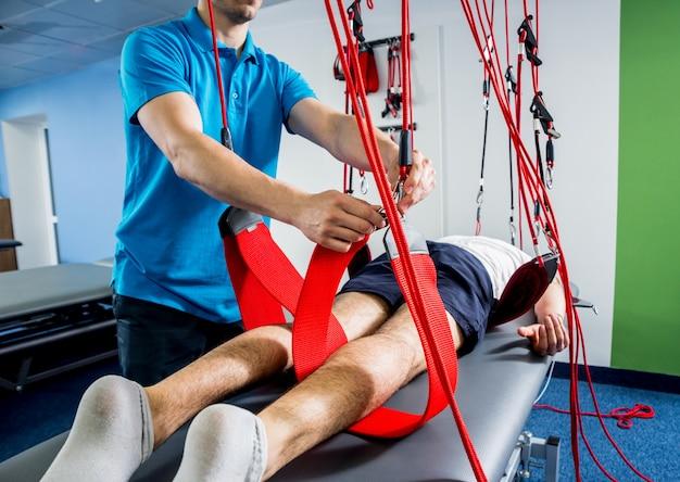 Fysiotherapie. oefentraining therapie. jonge man doet fitness tractie