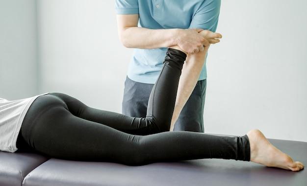 Fysiotherapiebehandelingen voor het piriformis-syndroom, fysiotherapeut strekt de bilspier van de vrouwelijke patiënt uit, post-isometrische ontspanning