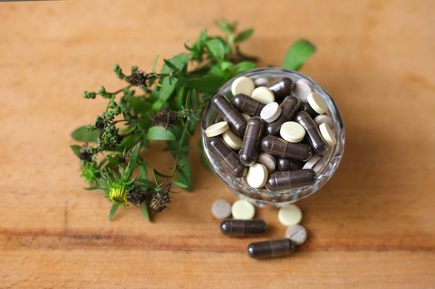 Fytocapsules in een glasplaat op een houten achtergrond. fytotherapie. kruidenbehandeling