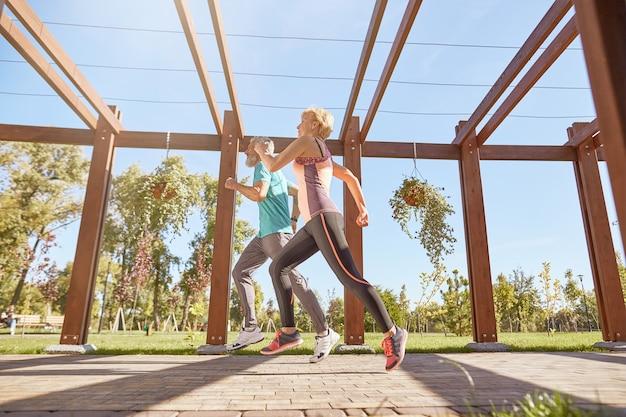 Ga gezond full-length shot van een actief volwassen familiepaar in sportkleding die samen joggen op een warme