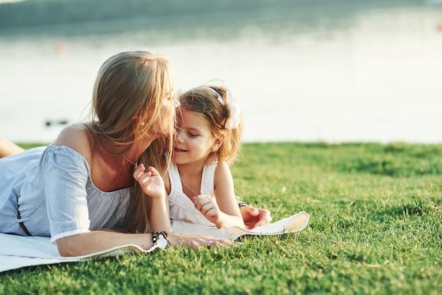 Ga liggen, het gras is prachtig. foto van jonge moeder en haar dochter die goede tijd hebben op het groene gras met meer bij achtergrond.
