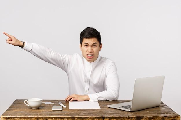 Ga mijn kantoor uit, ga. boze, agressieve en verontwaardigde aziatische mannelijke baas vraagt verlof, wijzend naar de uitgang en schreeuwde gehinderd, fronsend kijkend woedend, zittend bureau,