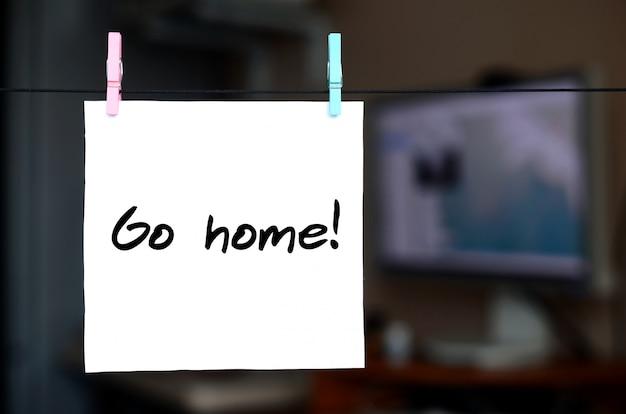 Ga naar huis! opmerking is geschreven op een witte sticker die met een wasknijper aan een touw op een achtergrond van kantoorinterieur hangt