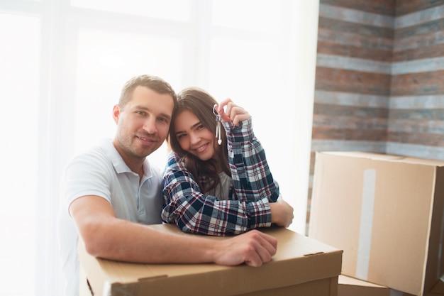 Ga naast kartonnen dozen staan en kijk naar de camera. in de handen van zijn vrouw de sleutels van een nieuwe woning, appartement, huis.
