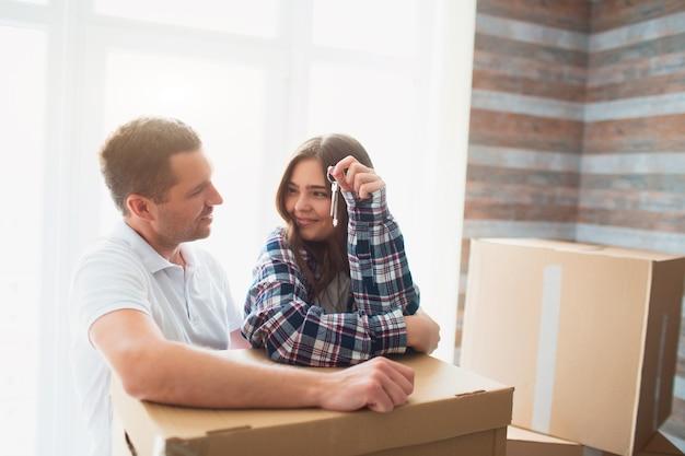 Ga naast kartonnen dozen staan en kijk naar elkaar. in de handen van zijn vrouw de sleutels van een nieuwe woning, appartement, huis