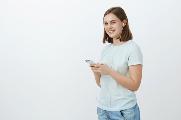 Ga nooit de deur uit zonder muziek. portret van charmante vriendelijk ogende opgetogen jonge vrouw in casual outfit klaar lopen naar universiteit oortelefoon dragen en smartphone glimlachend opzij te houden
