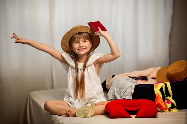Ga op avontuur en reis gelukkig klein meisje bereidt zich voor op de reis die de dochter haar koffers en een reistas aan het inpakken is