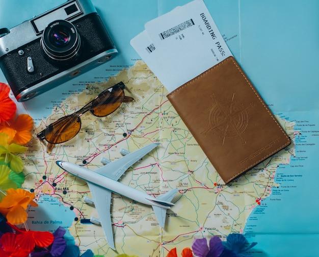 Ga op avontuur. kaart, vliegtuig, camera, bril en paspoort met kaartjes op tafel. reizen, vakantie concept. bovenaanzicht.