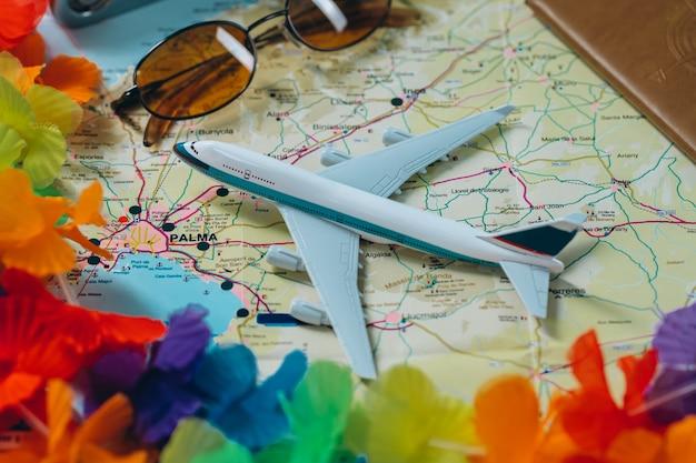 Ga op avontuur. kaart, vliegtuig, camera, bril en paspoort op tafel. reizen, vakantie concept.