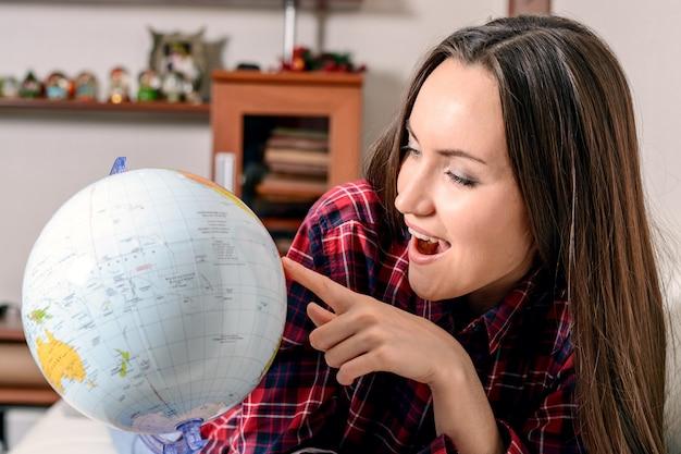 Ga op avontuur, vrouw droomt ervan om de wereld rond te reizen, kijkend naar de globe in de kamer van het huis, happy schattige brunette bereidt zich voor op de reis,