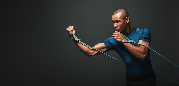 Ga sportman trainen met weerstandsband over donkere achtergrond