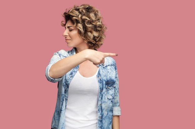 Ga weg. portret van een boze jonge vrouw met krullend kapsel in een casual blauw shirt dat staat en de richting van de uitgang toont. indoor studio opname, geïsoleerd op roze achtergrond.