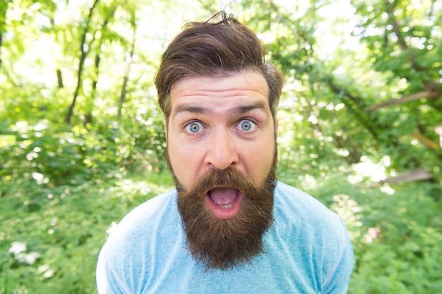 Ga wild. gekke bebaarde man in natuurlijke omgeving. hipster met lange baard emotionele gezicht close-up natuur achtergrond. haarverzorging mannelijke schoonheid. zomerplezier. bebaarde man in parkbos. bebaarde hipster.