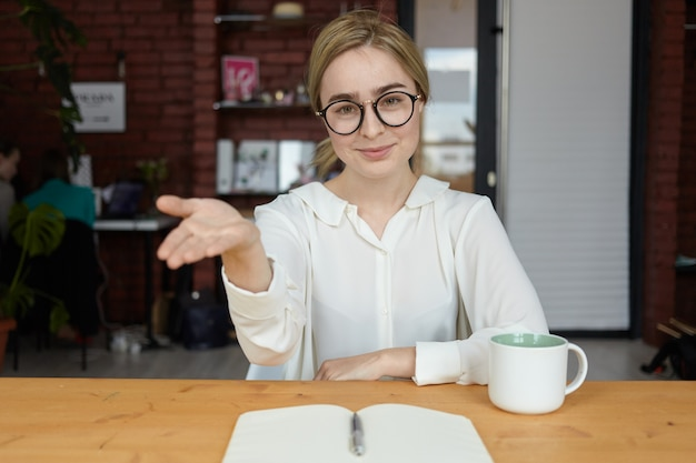 Gaat u zitten. binnen schot van mooie vriendelijk ogende jonge blanke zakenvrouw in brillen glimlachend en welkom gebaar maken tijdens zakelijke bijeenkomst met partner of klant in café