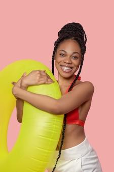 Gaat zwemmen. mooie afro-amerikaanse vrouw die een gele buis vasthoudt en er leuk uitziet