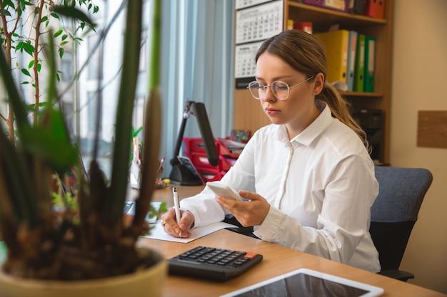 Gadgets gebruiken. kaukasische ondernemer, zakenvrouw, manager die geconcentreerd op kantoor werkt. ziet er serieus en druk uit, gekleed in klassieke kleding. concept van werk, financiën, zaken, succes, leiderschap.