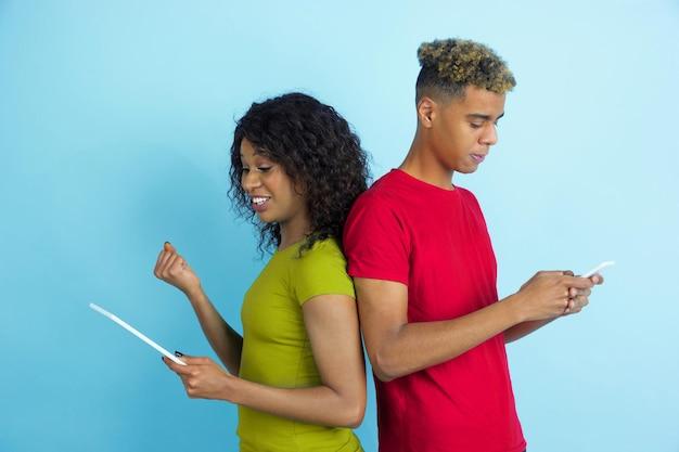 Gadgets gebruiken, lachen. jonge emotionele afro-amerikaanse man en vrouw in kleurrijke kleding op blauwe achtergrond.