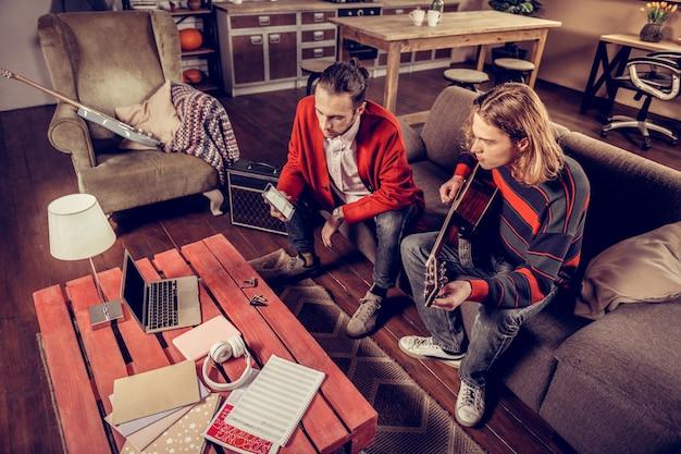 Gadgets gebruiken. moderne getalenteerde muzikanten die gadgets gebruiken terwijl ze in de woonkamer een nieuw nummer componeren