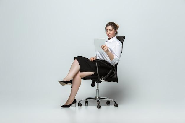 Gadgets. jonge vrouw in kantoorkleding. lichaamspositief vrouwelijk karakter, feminisme, van zichzelf houden, schoonheidsconcept. plus grootte zakenvrouw op grijze muur. baas, mooi. inclusie, diversiteit.