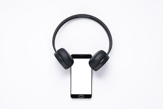Gadgets voor muziekliefhebbers, smartphone met wit scherm met draadloze koptelefoon.