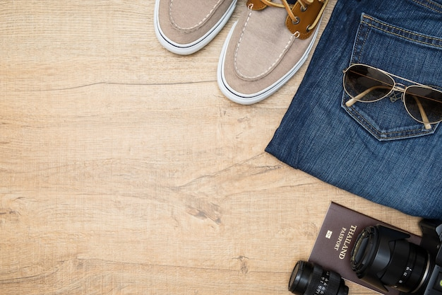Gadgets voor reizigers van de mens liggen op de houten tafel.