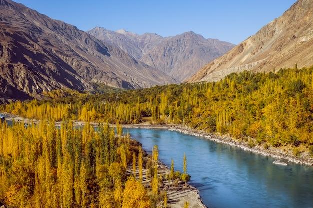 Gahkuch in de herfst toont rivierstroming door kleurrijk bos en omringd door bergen.