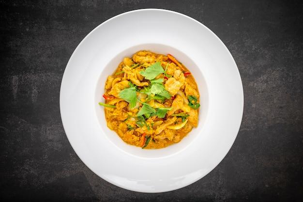 Gai pad pong karee, thais eten, roergebakken kip met kerriepoeder in eenvoudige witte keramische plaat op donkere toon textuur achtergrond, bovenaanzicht