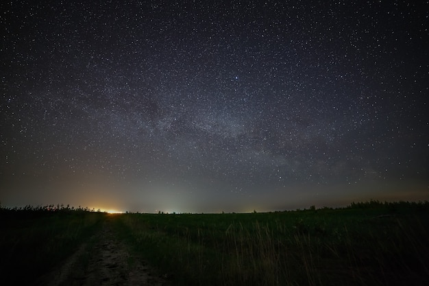 Galaxy de melkweg in de nachtelijke hemel met sterren. landelijke weg in de schemering. kosmische ruimte boven het aardoppervlak. lange blootstelling.
